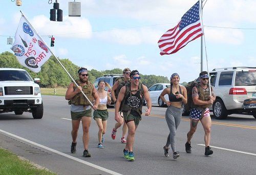 Runners carry the American and Armed Forces flag down Alabama 59 in Summerdale on Monday, May 25 to honor fallen service members for the annual Baldwin County Memorial Day Flag Relay.