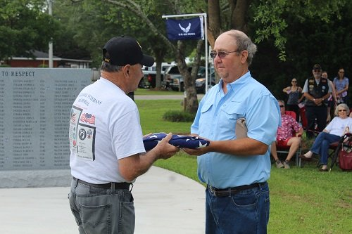 Organizer Frankie Kucera presents an American Flag to Roger Utter, son of longtime Silverhill resident Ralph Utter, a veteran of the U.S. Navy and U.S. Air Force, who died May 4 at the William F. Green Veterans Home in Bay Minette.