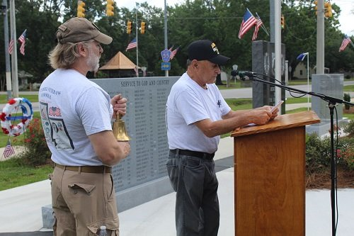 Frankie Kucera reads the names and eulogizes the six veterans while Joel Sterling rings a bell in their honor.