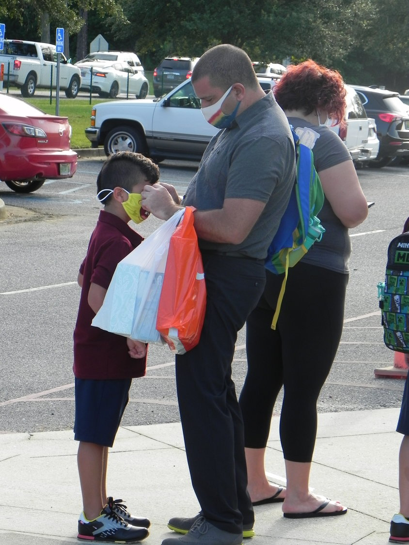 A parent adjusts the mask of a Robertsdale Elementary School student on the first day of classes Wednesday.