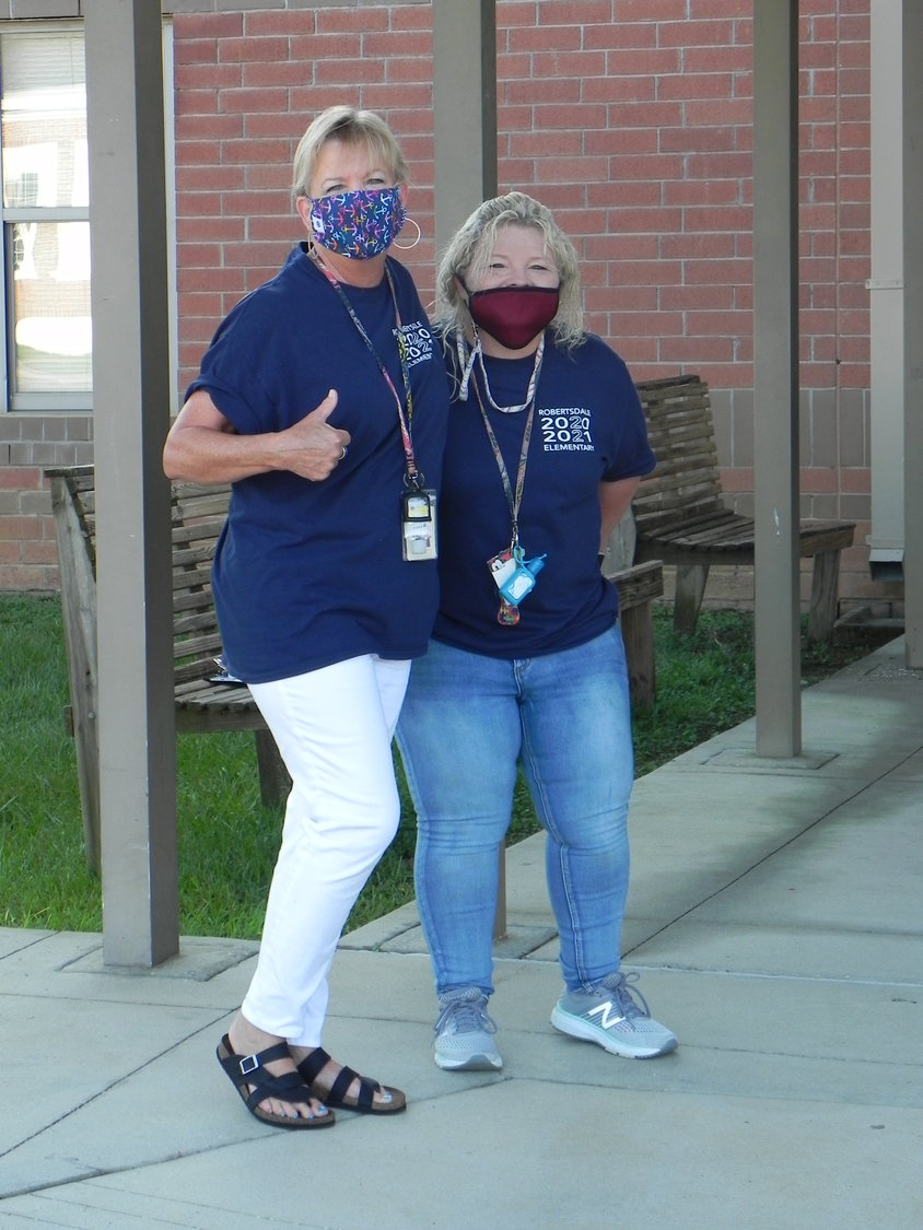 """We're smiling, really!"" Faculty members at Robertsdale Elementary School greeted students on the first day of school Wednesday."