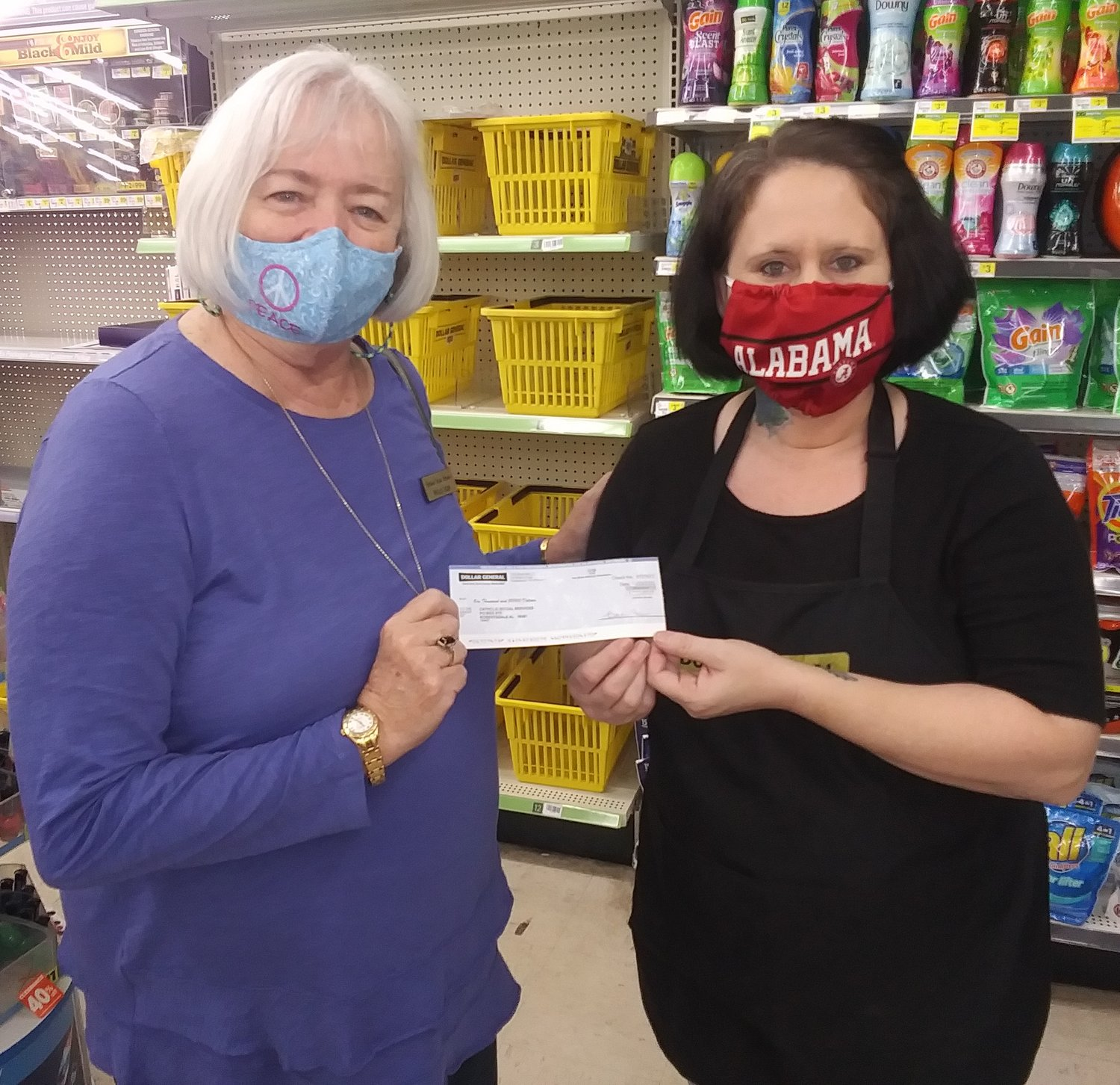 Lisa Cooper, an employee at Dollar General in Summerdale, presents a $1,000 check to Phyllis Beam, director of Catholic Social Services in Baldwin County. The donation was part of Dollar General's Kindness Award program.