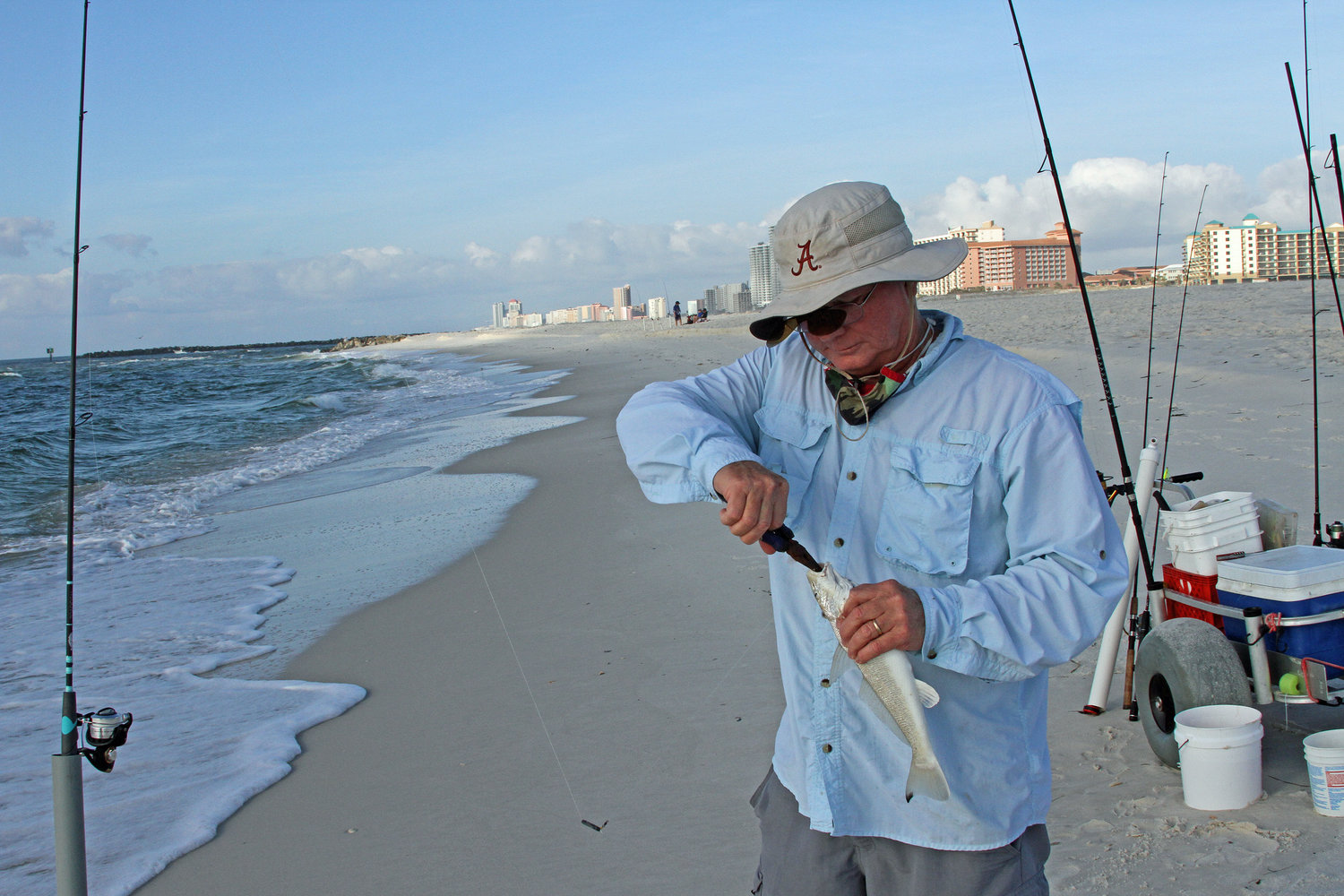 Thornton uses a suction pump to extract ghost shrimp from the surf to catch a variety of fish species.