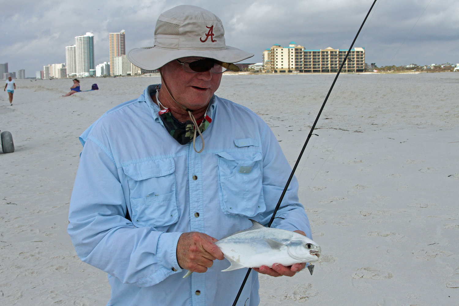 David Thornton of Mobile unhooks a nice whiting that hit a ghost shrimp in the surf at Orange Beach.