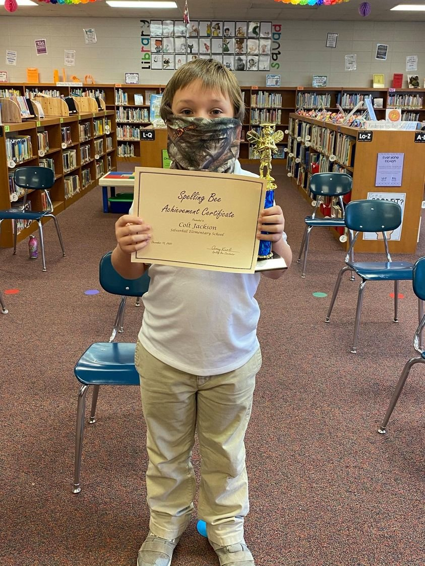 2021 Baldwin County Spelling Bee winner Colt Jackson of Silverhill Elementary poses with his trophy and certificate in the school's library.