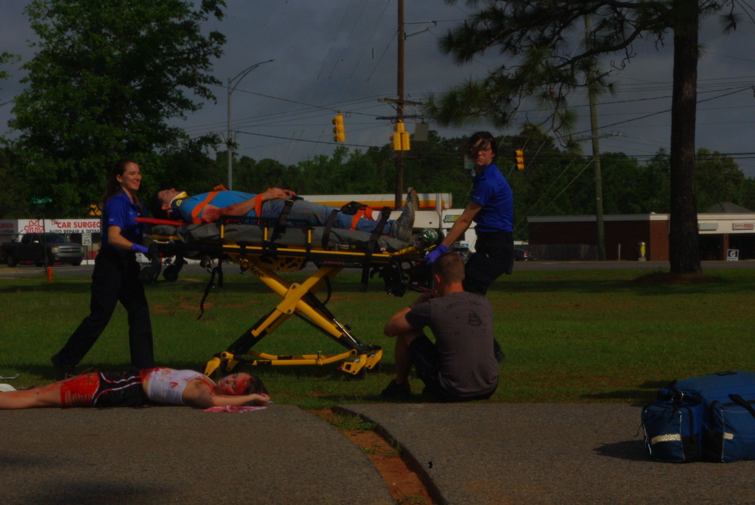 Paramedics load an accident victim on a gurney during a distracted driving accident simulation at Daphne High School.