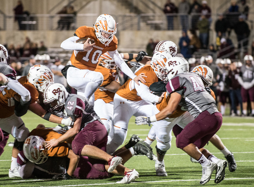 Westwood Warriors quarterback Will Jennings (10) leaps a group of Round Rock defenders in Friday night's comeback victory over the Dragons at Kelly Reeves Stadium.