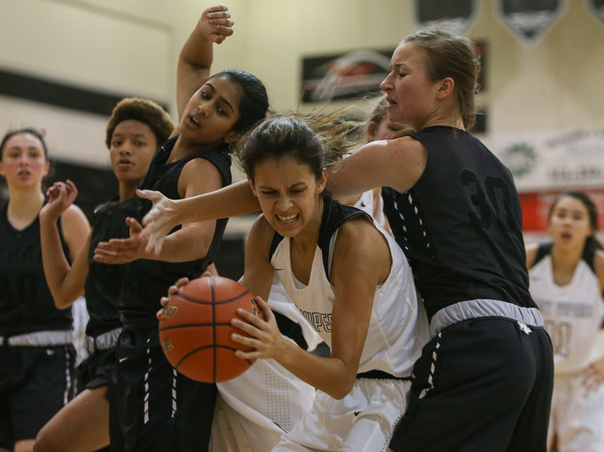 Vandegrift Vipers point guard Bee Gonzales (2) wrestles a rebound away from a group of Cedar Park players during a girls high school basketball game between the Vandegrift Vipers and the Cedar Park Timberwolves at Vandegrift High School in Austin, Texas on November 14, 2017.