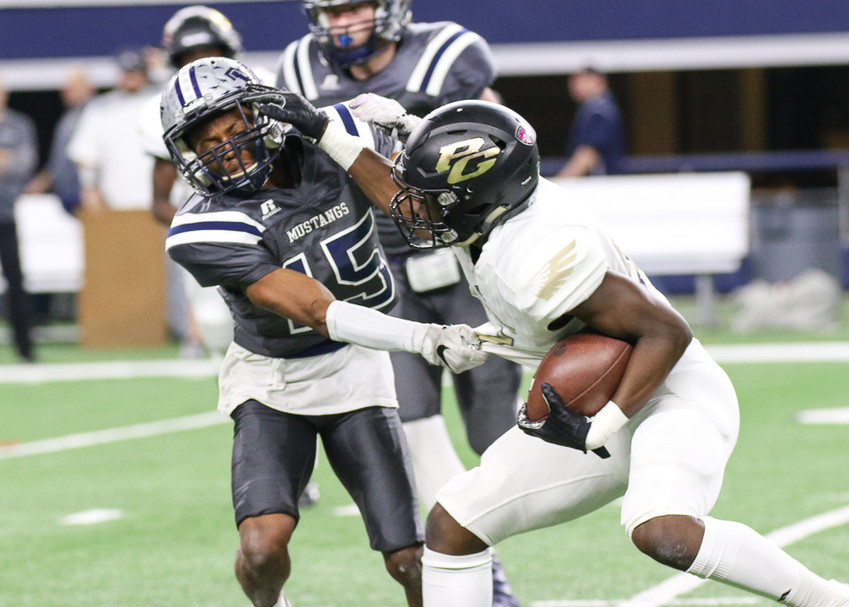 Pleasant Grove Hawks senior running back Chauncey Martin (21) delivers a stiff arm to West Orange-Stark Mustangs senior Jarron Morris (15) during the UIL Class 4A Division II state football championship game between West Orange-Stark High School and Pleasant Grove High School at AT&T Stadium in Arlington, Texas, on December 22, 2017.