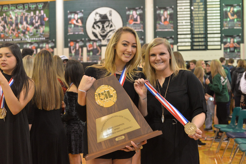 Cheerleading captain Sabrina Enriquez and coach Morgan Maddux celebrate with the state UIL Championship trophy.