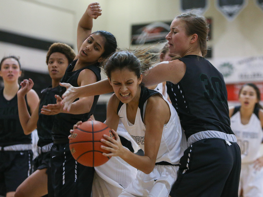 Vandegrift Vipers point guard Bee Gonzales (2) wrestles a rebound away from a group of Cedar Park players during a girls high school basketball game between the Vandegrift Vipers and the Cedar Park Timberwolves at Vandegrift High School in Austin, Texas on Nov. 14, 2017.