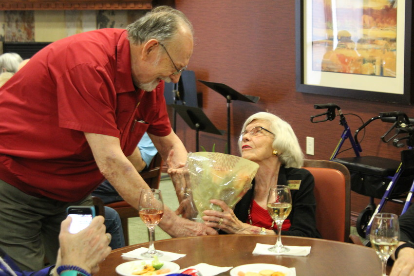 Andy Carver (left) presents Billie Tips (right) with a bouquet of flowers during social hour at Lakeline Oaks in Cedar Park, Friday, Feb. 2. Carver has made it a weekly tradition to buy flowers for widowed women in the retirement community in tribute to his wife.