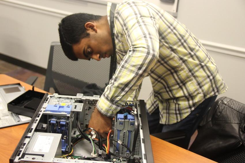 Cedar Park High School senior Rithvik Saravanan studies the interior of a Dell computer and puts it together.