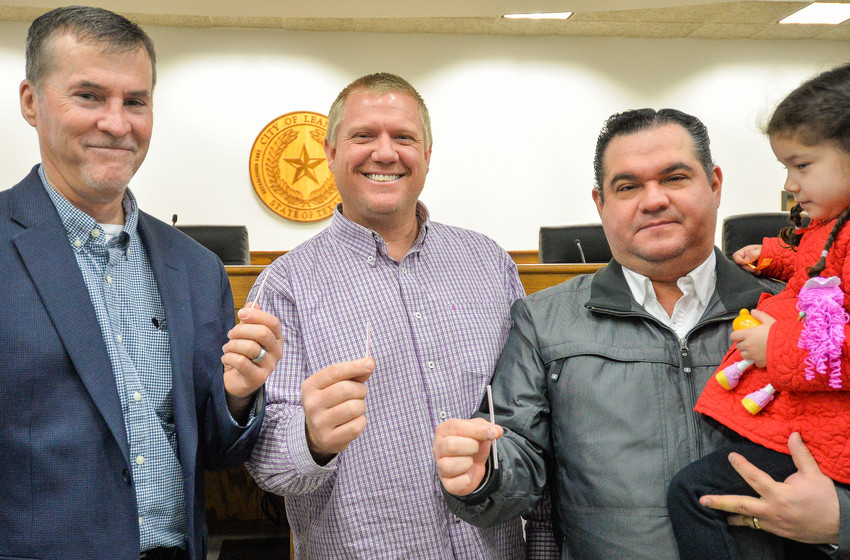 City of Leander candidates for mayor (left to right) Troy Hill, Adam Benefield and Vic Villarreal (holding his daughter) show the straws they drew for ballot position.
