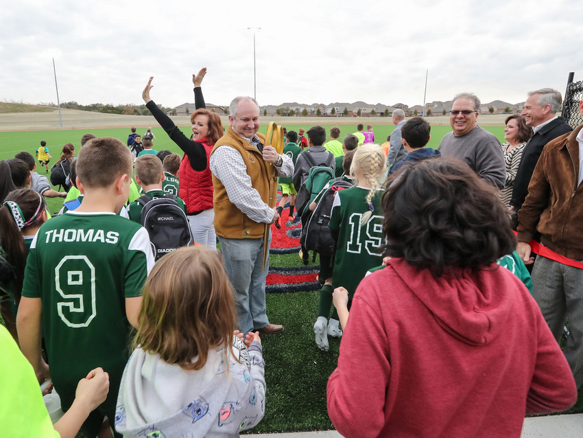 Mayor Chris Fielder stands aside as Leander Youth Soccer League players rush the field after the ribbon cutting ceremony at Robin Bledsoe Park in Leander, Thursday, Feb. 8.