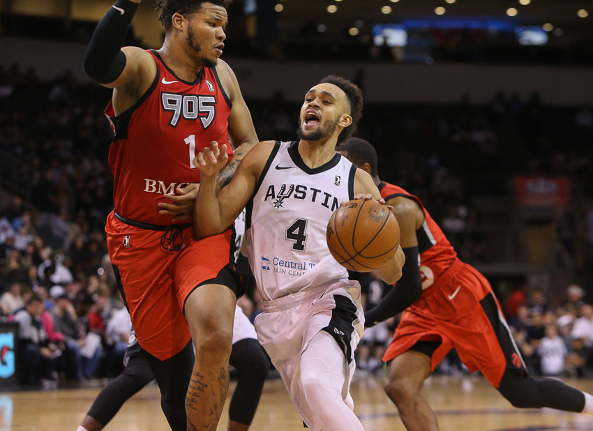 Austin Spurs guard Derrick White (4) moves the ball against Raptors 905 center Kennedy Meeks (1) during Game 1 of the NBA G-League finals between the Austin Spurs and the Raptors 905 at HEB Center in Cedar Park, Texas, on April 8, 2018.