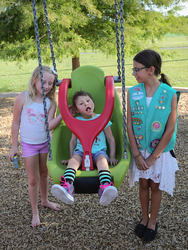 Emma Brown of Leander enjoys a swing on Leander's first installed adaptive swing at Robin Bledsoe Park. Emma is joined by sister Allison (left) and Olivia Garcia of Girl Scout Troop 2504.