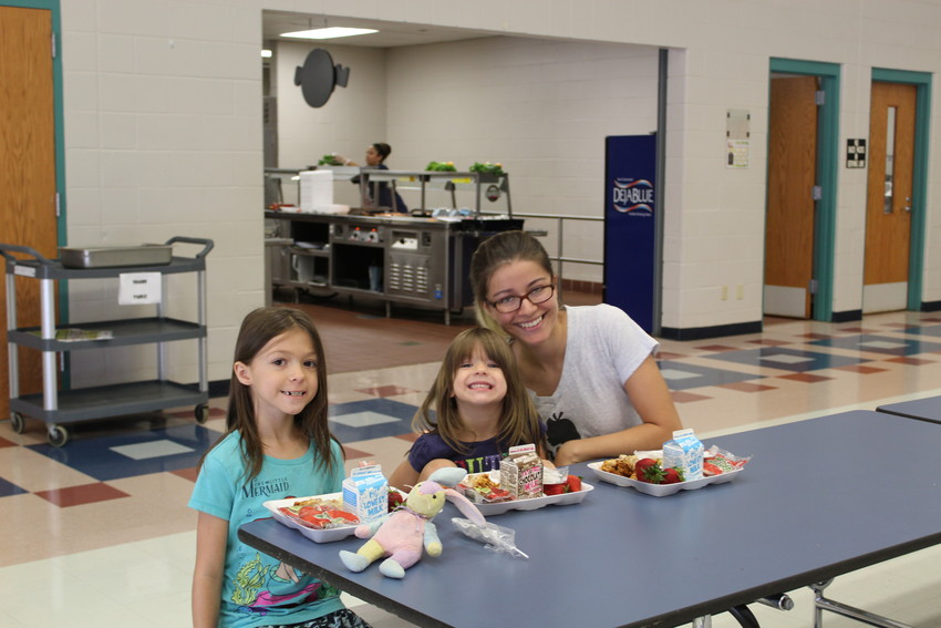Cedar Park resident and Leander High School sophomore Laryssa Gross-Ellis, 15, enjoys lunch with her two younger sisters Roguen Dodd, 7, (left), and Danika Dodd, 4, (center) at Running Brushy Middle School on June 20.
