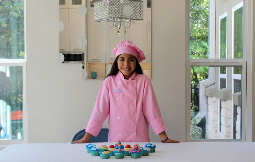 Twelve-year-old Ava Avila shows off several of her best-selling beach-themed cupcakes at her Round Rock home.