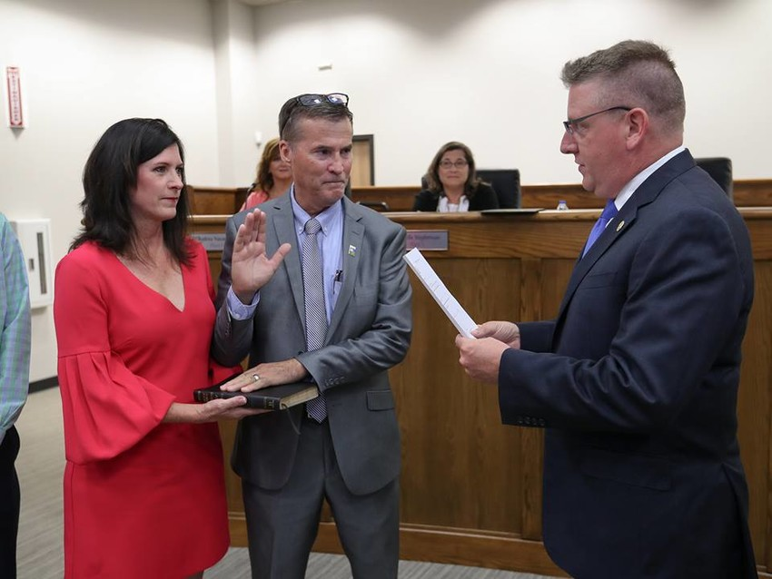 Newly-elected Leander Mayor Troy Hill stands with wife Sally as Texas State Representative Tony Dale conducts the oath of office during the July 5 Leander City Council meeting.