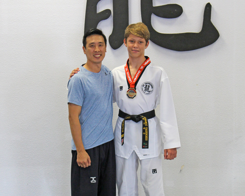 Master Hyun Kim, owner of HK Taekwondo in Cedar Park poses with Zachary Hampton, who recently won a gold medal at the USA Taekwondo National Competition in Salt Lake City.
