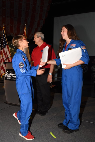 Incoming Wiley Middle School student Mason Azios, 11, of Leander, shakes hands with a camp trainer during Space Camp' graduation ceremony July 19.