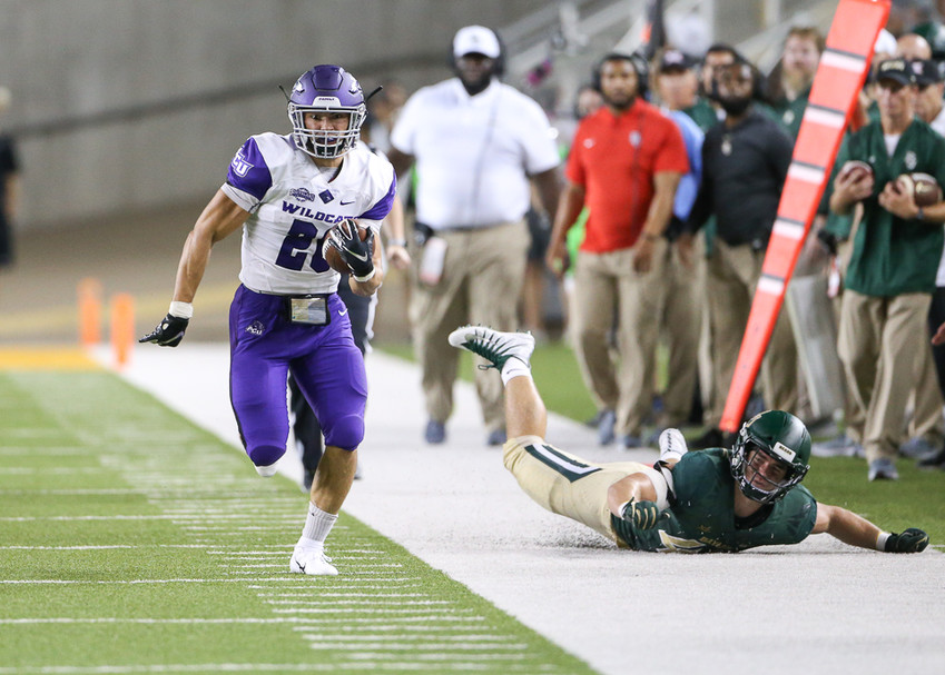 Abilene Christian Wildcats running back Billy McCrary (20) carries the ball on a 75-yard touchdown run as Baylor Bears linebacker Chad Kelly (49) looks up from the turf in the second quarter of an NCAA football game between Baylor University and Abilene Christian University on Saturday, Sept 1, 2018 in Waco, Texas.