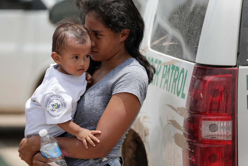 A woman from Honduras carries her baby after surrendering to border patrol agents on June 25, 2018, near Granjeno, Texas.