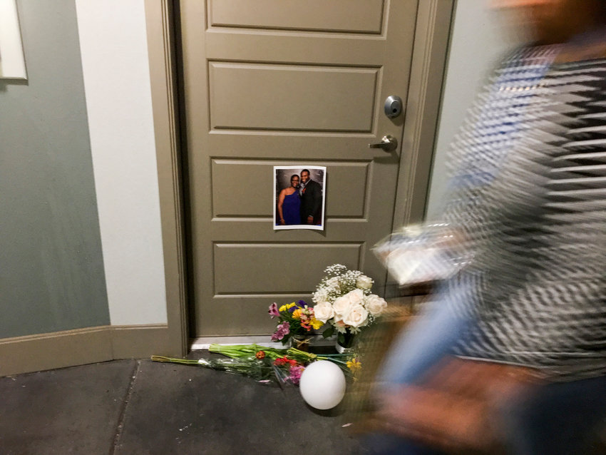 A resident passes flowers at the front door of Botham Shem Jean, who Dallas police say was shot by Amber Guyger, an off-duty police officer who said she mistakenly thought her apartment was his, as photographed on September 10, 2018, at the South Side Flats in Dallas.