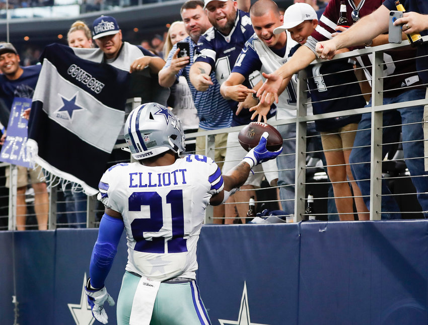 Dallas Cowboys running back Ezekiel Elliott (21) gives the football to a fan following his touchdown against the Detroit Lions during the first half on Sunday, Sept. 30, 2018 at AT&T Stadium in Arlington, Texas.