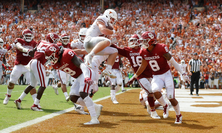 Texas quarterback Sam Ehlinger (11) leaps over Oklahoma linebacker Kenneth Murray (9) to score a touchdown during the second half at the Cotton Bowl in Dallas on Saturday, Oct. 6, 2018. The loss to Texas cost Oklahoma defensive coordinator Mike Stoops his job.