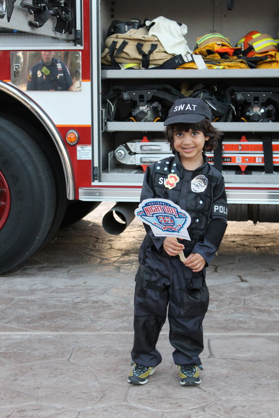 Four-year-old Kai Jivani of Mason Hills shows off his spiffy SWAT uniform in front of a Leander firetruck on National Night Out Oct. 2