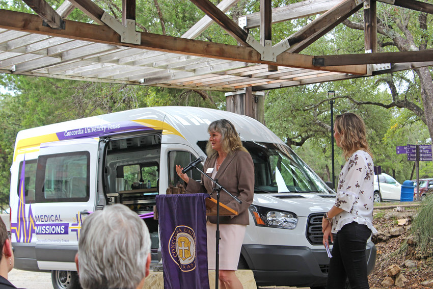 Dr. Greta Degan commemorates Concordia University's new nursing van as former student Caitlin Rowlette looks on at a dedication ceremony held on Sept. 28