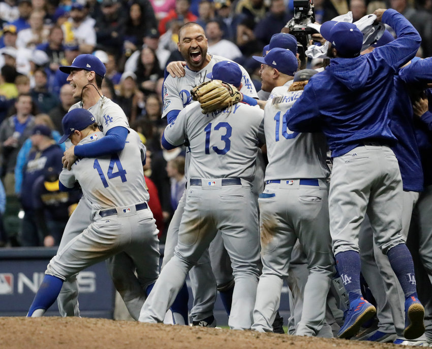 The Los Angeles Dodgers celebrate a 5-1 win against the Milwaukee Brewers in Game 7 of the National League Championship Series at Miller Park in Milwaukee on Saturday, Oct. 20, 2018.