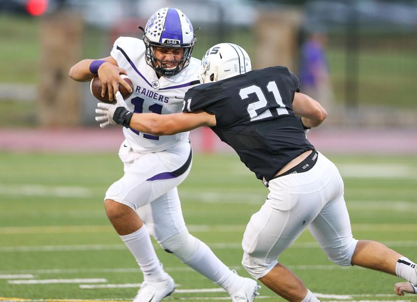 Cedar Ridge Raiders junior quarterback Jalen Brown (11) attempts to elude Vandegrift Vipers junior Jax Mccauley (21) during a high school football game between Vandegrift and Cedar Ridge on Friday, Sept. 14, 2018 in Austin, Texas.