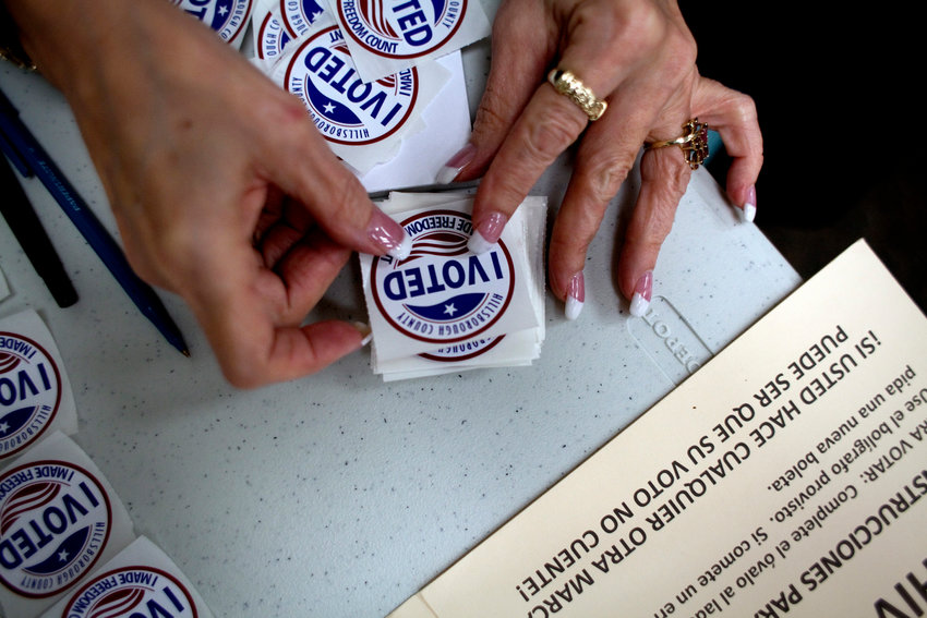 """A poll worker prepares """"I Voted"""" stickers to hand to voters as they finished up at the ballot booths."""