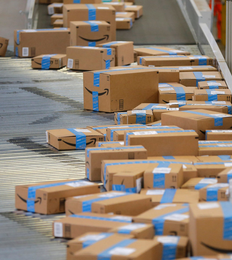 Packed and sealed boxes move toward the trucks as employees fill orders at Amazon Fulfillment Center in Haslet, Texas