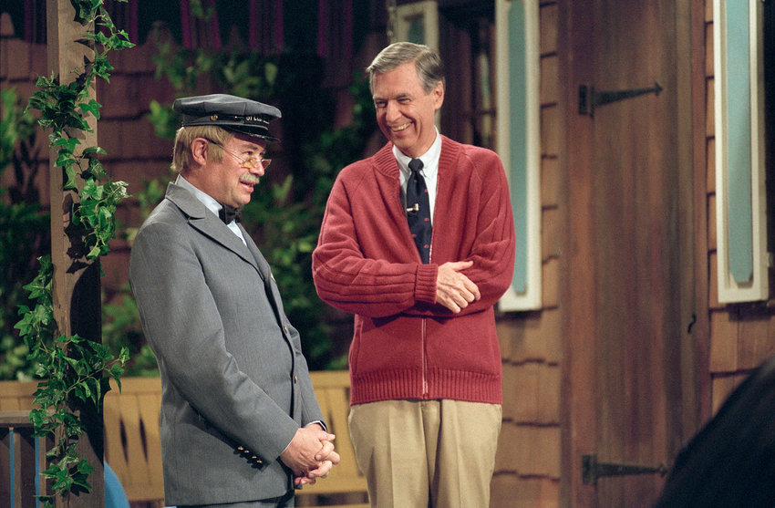 "Fred Rogers and David Newell, as Speedy Delivery's Mr. McFeely, stand on the front porch set while filming an episode of ""Mister Rogers' Neighborhood."""