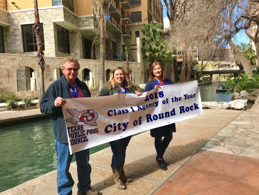 Pool Tech Layne Elbers, Aquatics Manager Nichole Bohner and Aquatics Supervisor  Michelle Weydert hold a banner recognizing the city's Aquatics Division being named Agency of the Year by the Texas Public Pool Council.