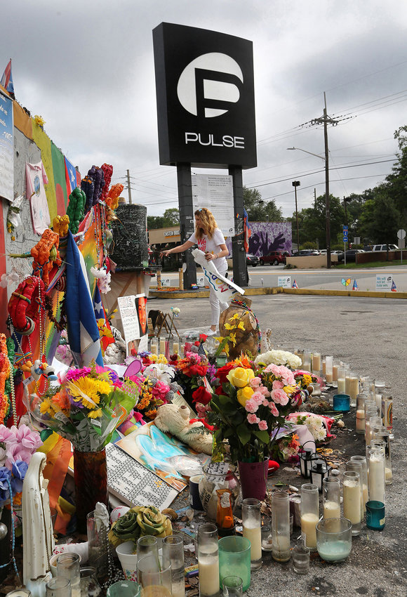 Pulse nightclub owner Barbara Poma tends to the memorial in front of her club on June 10, 2017, in Orlando, Fla.