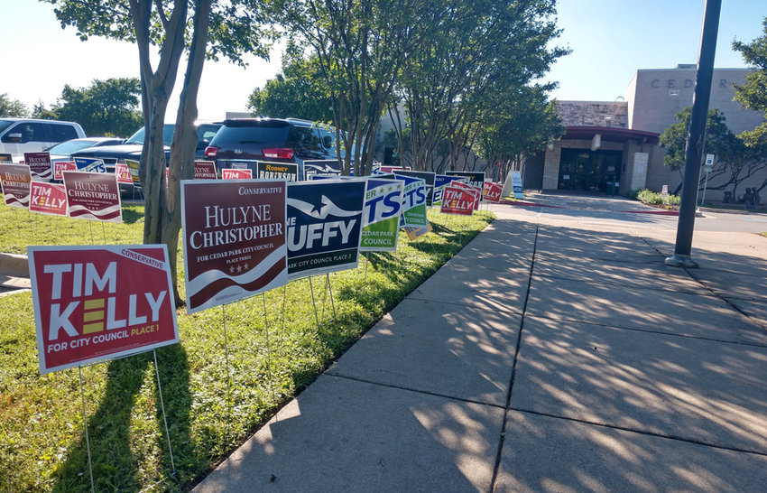 Campaign signs line the walkway outside the Cedar Park Public Library on Thursday, April 25, 2019.