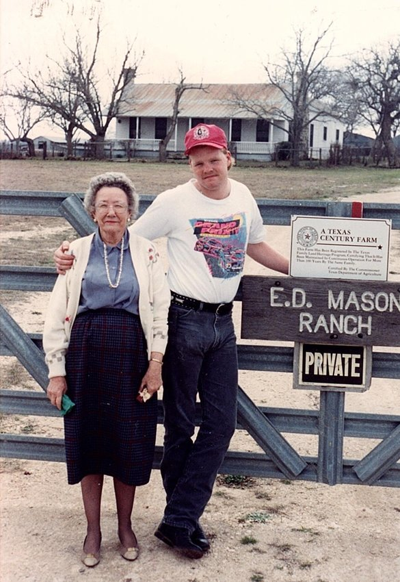 A 1990 photo of Christine Mason and Mason Thompson at the gate of the Mason Homestead with the Texas Department of Agriculture 100 year centennial sign, which signifies that a single family has owned the farm for 100 years or more.