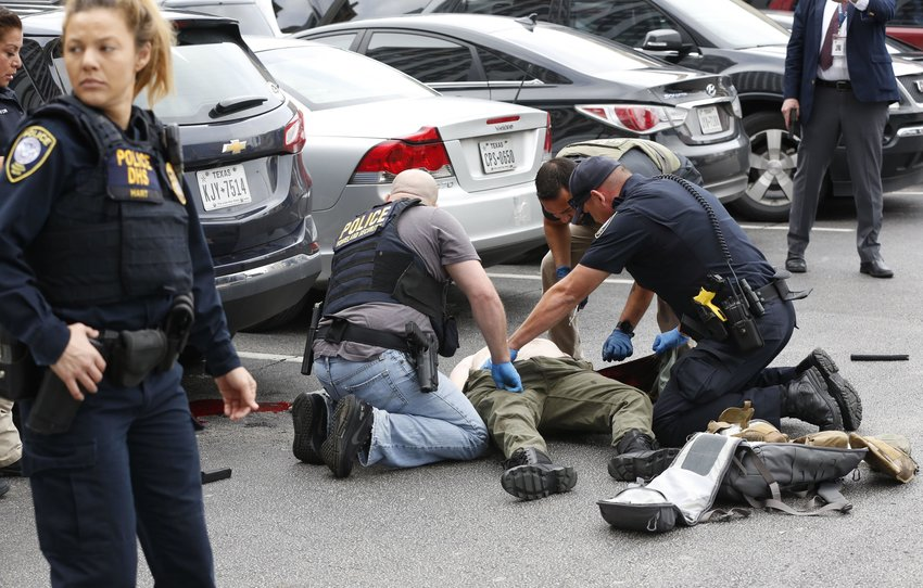 Law enforcement officers attend to an injured shooter in a parking lot after he fired shots at the Earle Cabell Federal Building in downtown Dallas on Monday.