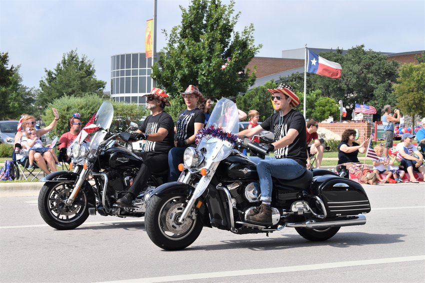 People on motorcycles ride past attendees at the Cedar Park Forth of July Parade on Thursday.