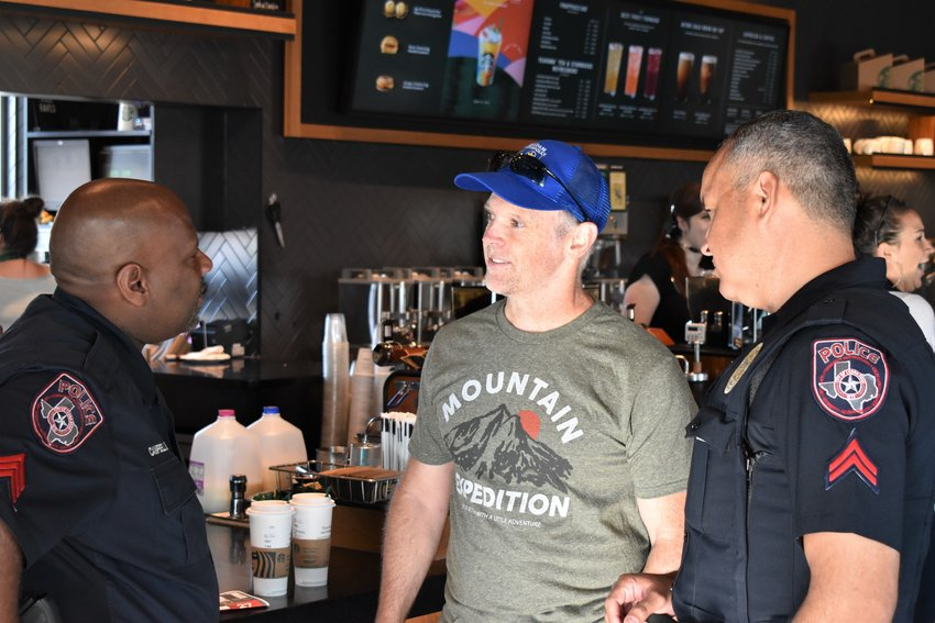 Sgt. Jessie Campbell and Corporal Ricky Pando of the Cedar Park Police Department talk to a citizen after he received his order from Starbucks staff.