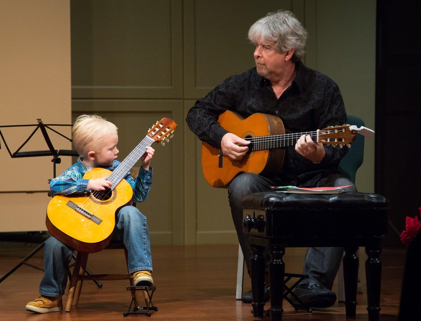 Slobodan Vujisic plays guitar with a student of the Childbloom Guitar Program.