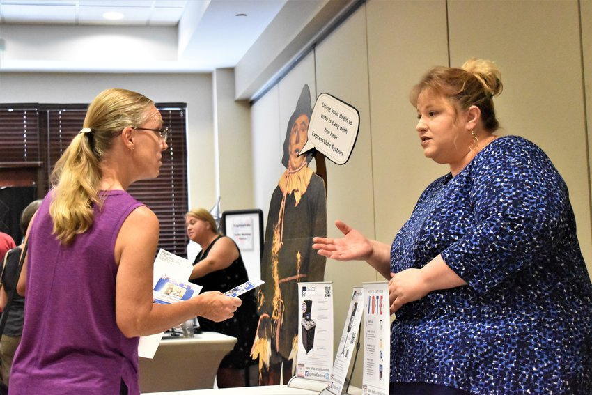 An attendee speaks with a Williamson County staff member at the showcase on Wednesday about new voting systems being implemented for upcoming elections.
