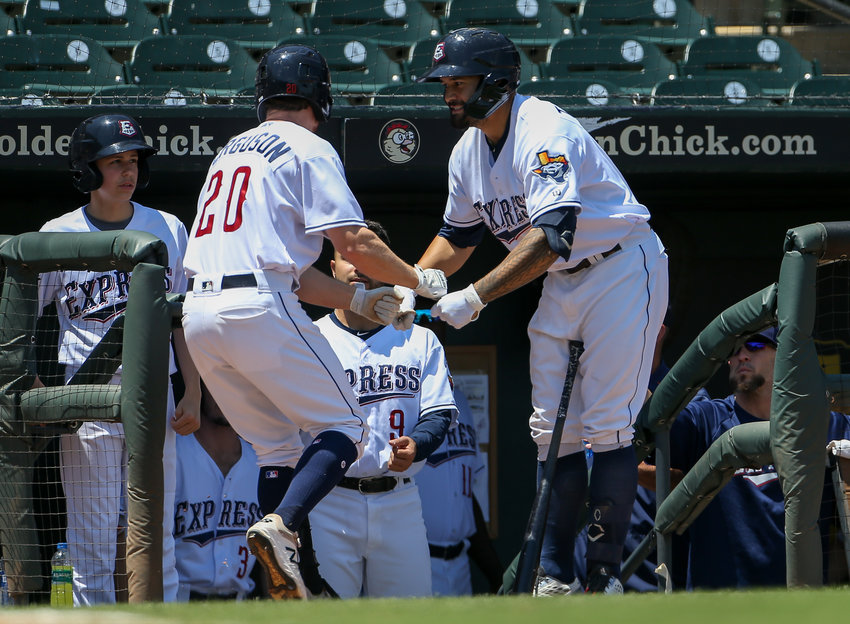Round Rock Express third baseman Nick Tanielu (21) congratulates outfielder Drew Ferguson (20) after a Ferguson's solo home run in the bottom of the second inning of a Minor League Baseball Game between the Round Rock Express and the New Orleans Baby Cakes on April 28, 2019 at Dell Diamond in Round Rock, Texas.