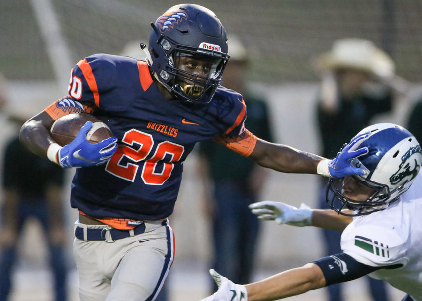 Glenn Grizzlies junior Jarvis Henderson (20) delivers a stiff arm while carrying the ball during a high school football game between Glenn and McNeil on Friday, Sept 7, 2018 in Cedar Park, Texas.
