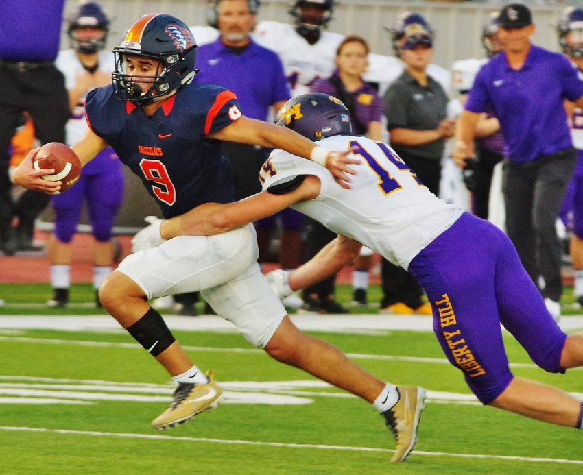 Glenn High School Grizzlies Quarterback Drew McGuire (9) under pressure from the Liberty Hill Panthers at Bible Stadium, Leander, Texas on August 30, 2019.